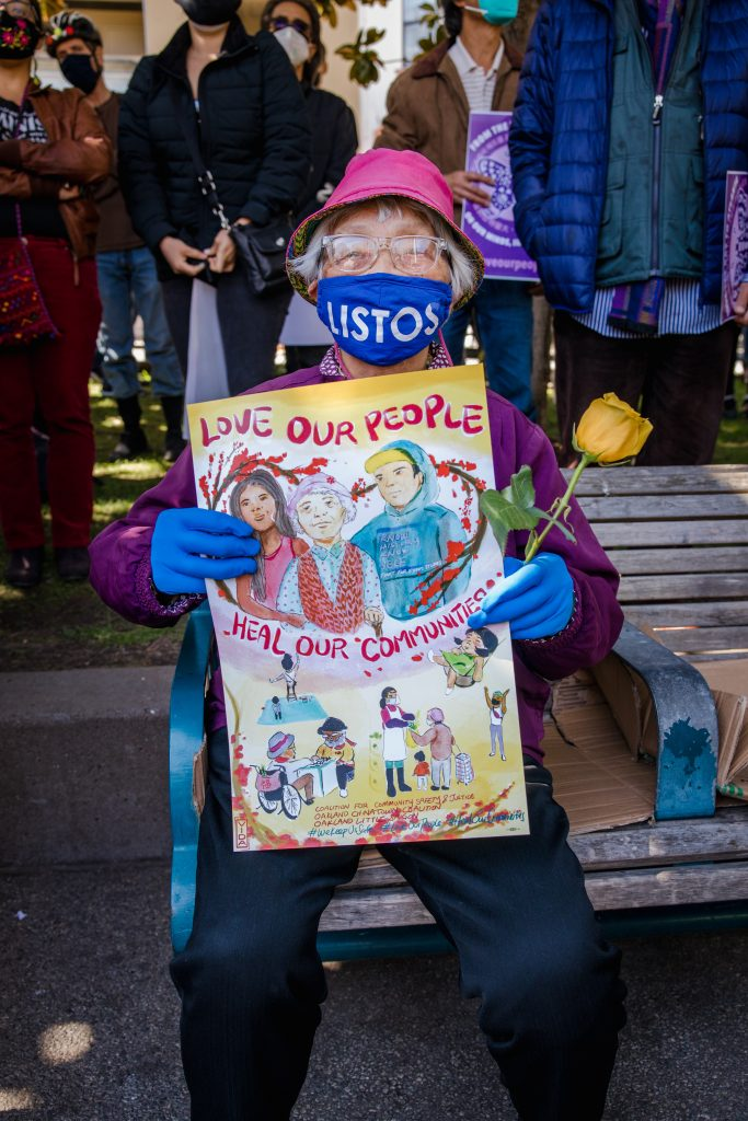 """Image of elder on a bench with a blue face mask an pink bucket hat. They are holding a sign and yellow rose. The has a drawing of a three people, with flowers surrounding them, and other drawings of people in community helping each other. The sign says """"Love our People, Heal our Community."""" They are wearing a purple jacket, with blue gloves."""